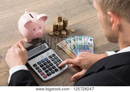 Close-up Of A Businessman Calculating Savings