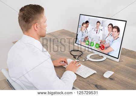 Male Doctor Video Conferencing On Computer