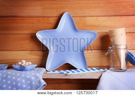 Blue star bowl with wafer cones and towels on wooden background