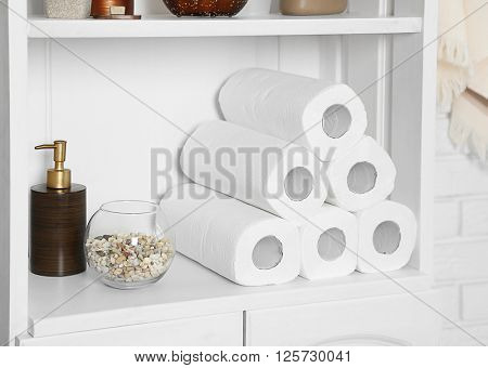 Bathroom set with paper towels and dispenser on a shelf in light interior