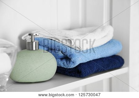 Bathroom set with towels and dispenser on a shelf on light interior