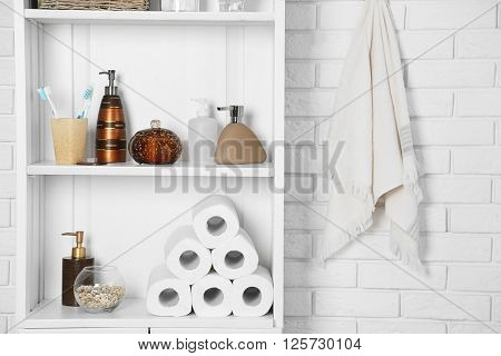 Bathroom set with toothbrushes, towels and dispensers on a shelf in light interior