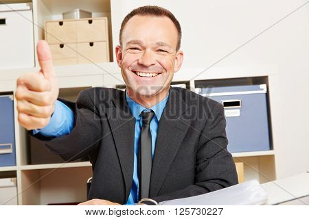 Successful happy business man holding thumbs up in his office