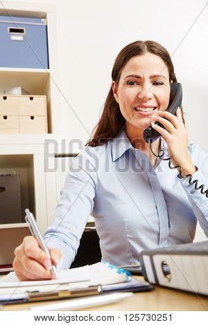 Business woman on the phone with customer support hotline taking notes