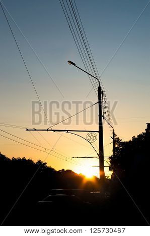 silhouette lamp street lighting of the road at dusk