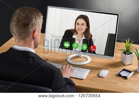 Young Businessman Video Conferencing With Colleague On Laptop At Desk In Office