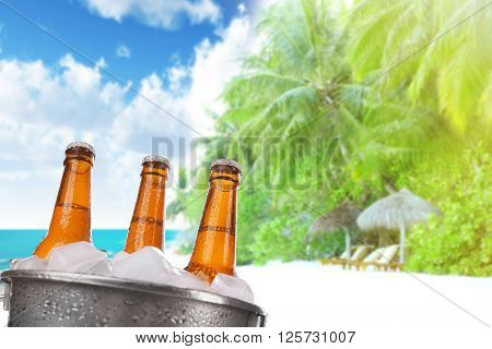 Beer bottles of cold fresh beer in ice bucket, on sea or ocean background