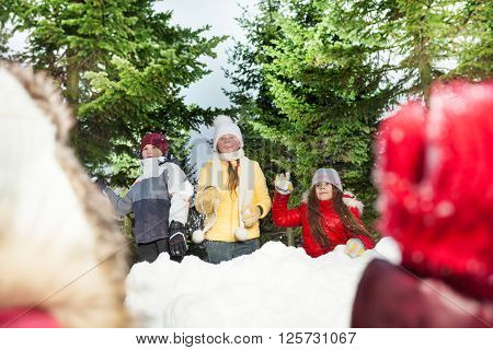 Happy friends, girls and boy playing snowballs hiding behind snow tower in the winter forest