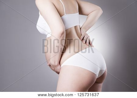 Caucasian pregnant woman in white lingerie with abdominal pain on gray studio background. Pregnancy concept