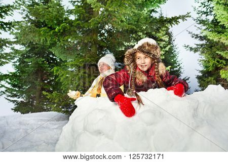 Cute girls playing the snowballs outdoors on a winter's day