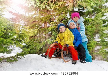 Three happy little kids on sledge in the park slide down on snow hill