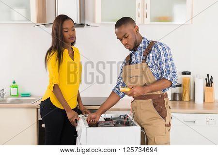 Serviceman Repairing Washing Machine