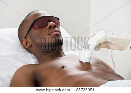 Therapist Giving Laser Epilation On Man's Chest