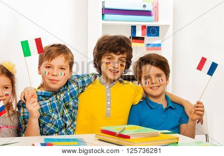 Four happy kids with flags on cheeks waving pennons sitting in the classroom