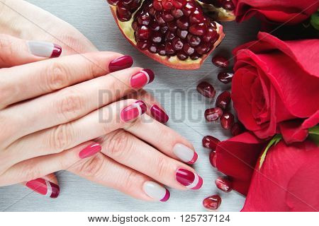 Skin care of a beauty female hands with grey pink and red asymmetry nail art manicure. And pockmarked grey background with red roses and sliced pomegranate