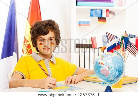 German schoolboy writing at copybook with pencil in light classroom