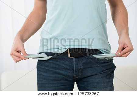 Close-up Of Young Man Showing Empty Pockets At Home