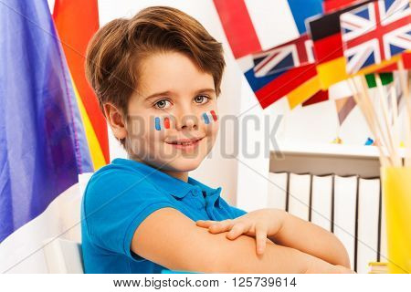 Portrait of diligent French schoolboy with flags on cheeks sitting at the classroom