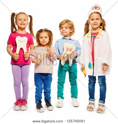 Four little children playing doctors with teeth dummies, toothbrush and stethoscope, isolated on white background