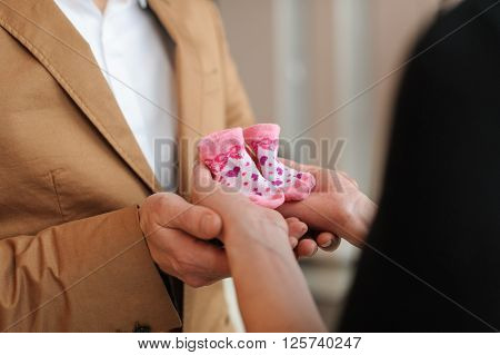 Pregnant woman holds pink booties. Beautiful pregnant woman and her husband in black dress and brown suit. Husband holds wife's hands with two booties.