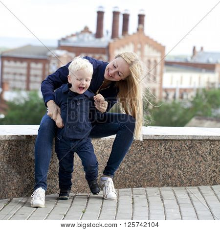 Beautiful young mother is holding her son in the summer park