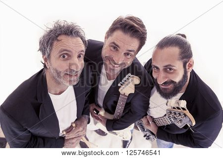 Portrait Of Rock Band Trio Embraced In The Studio
