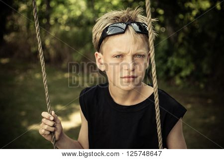 Boy In Black Shirt Sits Alone On Rope Swing
