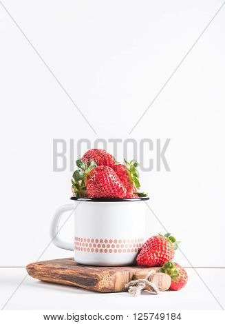 Fresh ripe red strawberries in country style enamel mug on rustic wooden board over white background, selective focus, vertical. Copy space