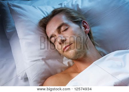 Young Man Sleeping in his Bed