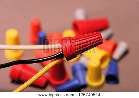 Wire connectors holding black, white, and yellow wires together