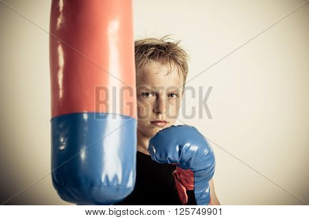 Frowning Blond Boy Stands Beside Punching Bag