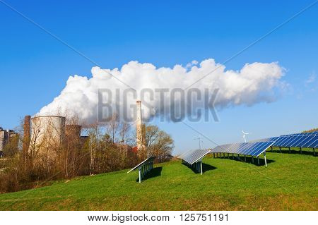 field with solar collectors and fossil-fuel power station