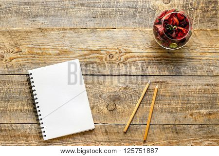 white notebook with pencil and flower sachets on wooden table