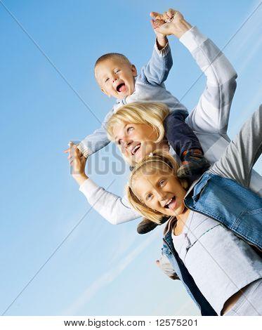 Mãe de Outdoor.Happy de família saudável com as crianças sobre o céu azul