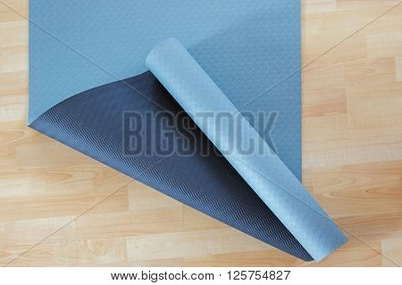 Thick anti slip blue and black fitness yoga practice or meditation mat made of PVC on yellow laminate wooden floor