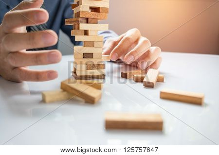 Planning risk and strategy in business businessman gambling placing wooden block on a tower