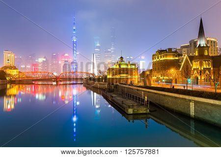 beautiful reflection in suzhou creekmisty shanghai skyline at night