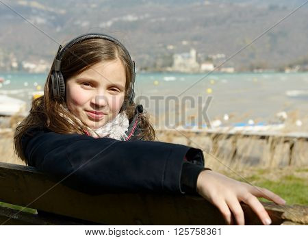 a young teenager listening to music on his phone outdoor