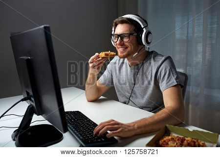 technology, gaming, entertainment, let's play and people concept - happy young man in headset with pc computer eating pizza while playing game at home and streaming playthrough or walkthrough video
