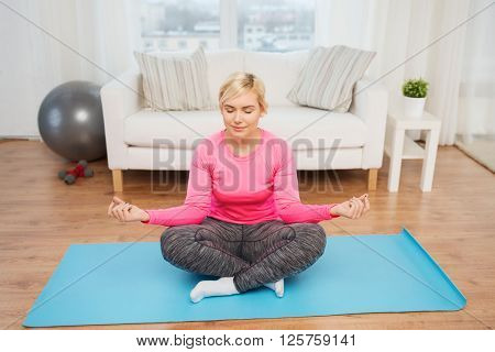 fitness, sport, people and healthy lifestyle concept - happy plus size woman stretching leg on mat at home