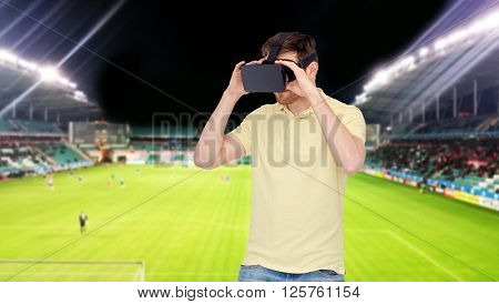 3d technology, virtual reality, sport, entertainment and people concept - young man with virtual reality headset or 3d glasses over football field on stadium background