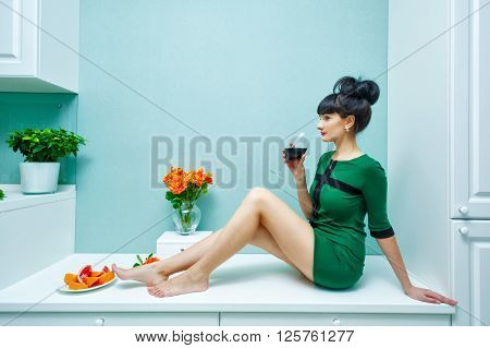 Young attractive woman drinking red wine at home.