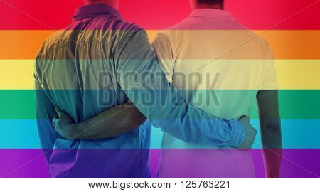 people, homosexuality, same-sex marriage, gay and love concept - close up of happy male gay couple hugging from back over rainbow flag stripes background