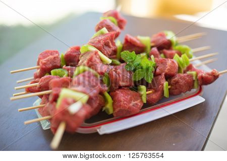 Marinated beef BBQ Skewers arranged with pepper and mint for decoration ready for grill. Classic kabob