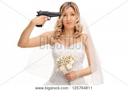 Young desperate bride holding a gun against her head and looking at the camera isolated on white background