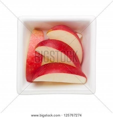 Slices of red apple in a square bowl isolated on white background