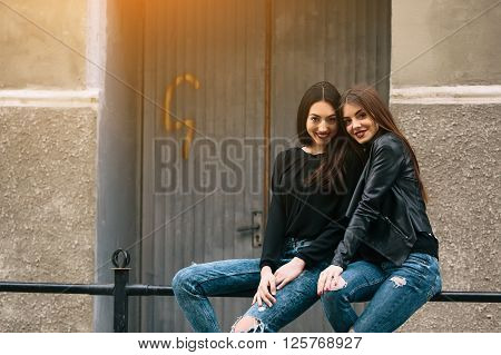 Two young adult women sitting on the railing and posing for the camera