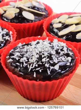 Homemade delicious fresh baked chocolate muffins with desiccated coconut and sliced almonds in red silicone cups lying on wooden cutting board concept for dessert