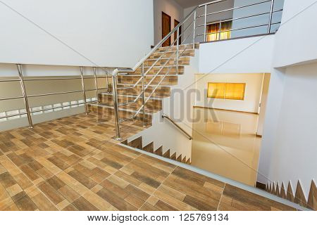 staircase in residential house with stainless steel banister ceramic floor tiles wood pattern