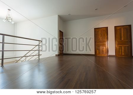 empty room white mortar wall background and wood laminate floor in residential
